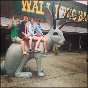 four people sitting on a large statue of a jackalope